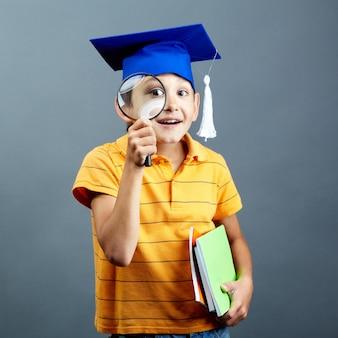 Улыбаясь студент играет с его лупой