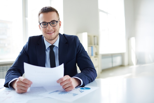 Сотрудник в очках держит отчет