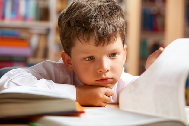 Крупным планом маленький мальчик читает книгу