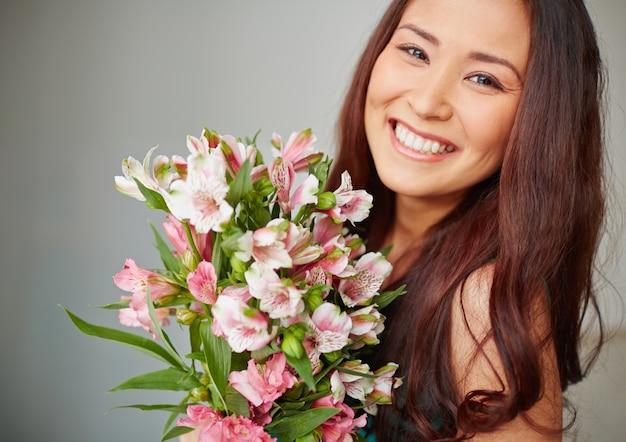 若い女性は花束と笑顔