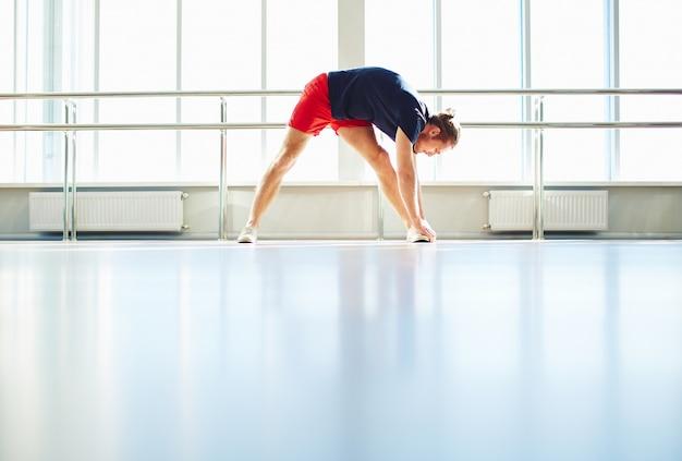 トレーニングセッションの前に足を伸ばしスポーツマン