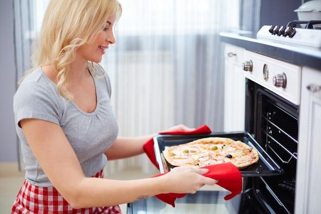 Женщина надевает пиццу в духовке