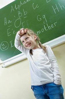 黒板の背景を持つ少女の笑顔