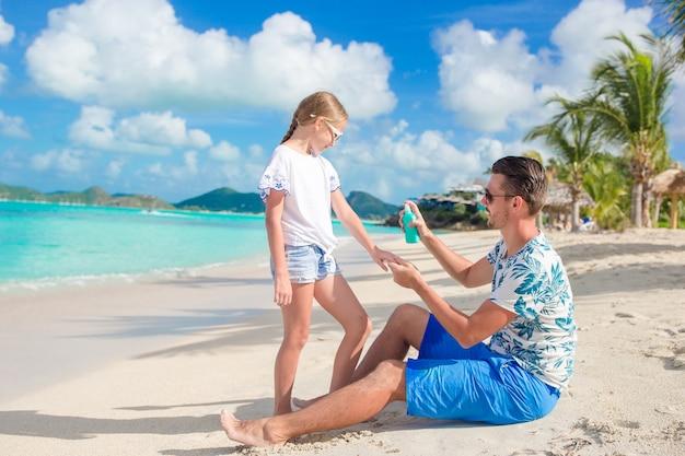 Молодой отец, применяя солнцезащитный крем для дочери