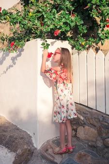 Девушка в белых платьях развлекается на улице на улице миконос