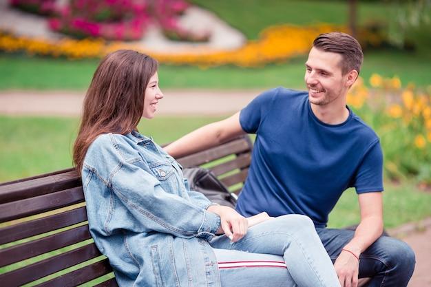 Расслабленная молодая семья на скамейке в парке
