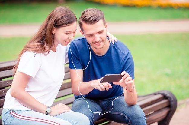 Пары используя таблетку и парк мобильного телефона публично.