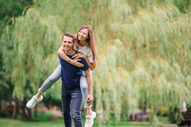 Расслабленная молодая семья на открытом воздухе в парке