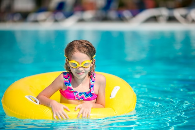 スイミングプールで楽しんで膨脹可能なゴム製サークルを持つ少女