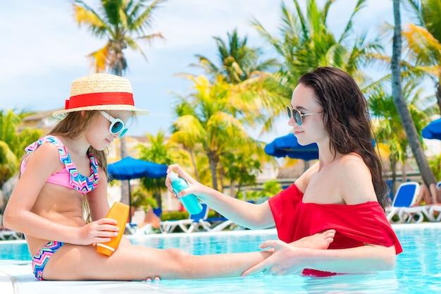Молодая мать наносит солнцезащитный крем на нос дочери в бассейне