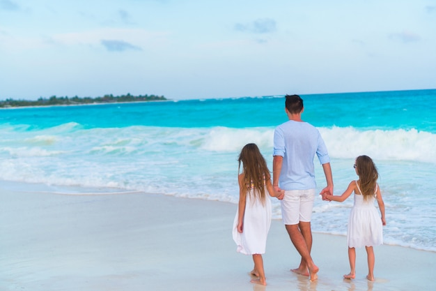 夕方にはカリブ海の島の白いビーチの上を歩く家族