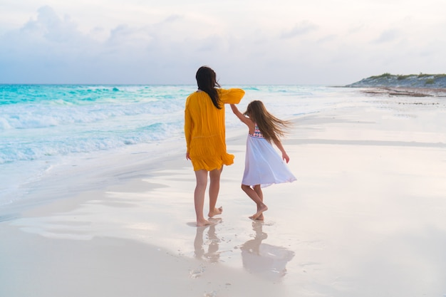 Маленькая прелестная девушка и молодая мать на тропическом пляже в теплом вечере