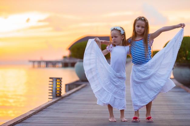 木製の桟橋で夕暮れ時のかわいい女の子