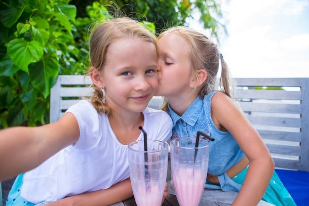 Маленькие девочки, делающие селфи и пьющие вкусные коктейли в тропическом курорте