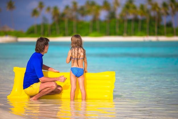 Маленькая девочка и молодой отец с надувной матрас на летние каникулы
