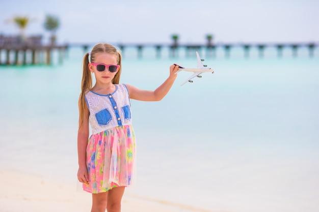 白い砂浜の手でおもちゃの飛行機を持つ少女