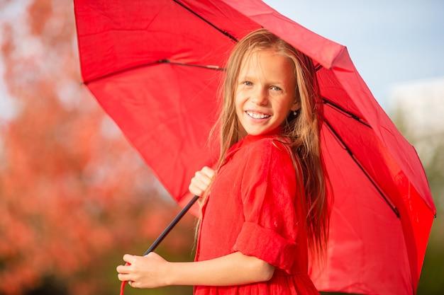 幸せな子供の女の子は赤い傘の下で笑う