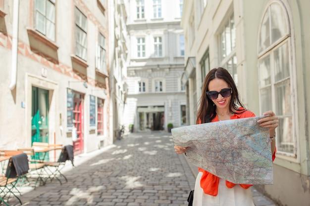 ヨーロッパでの休暇中に屋外ウィーンの地図で観光少女を旅行します。