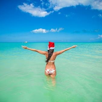 サンタ帽子の美しい若い女性の背面図
