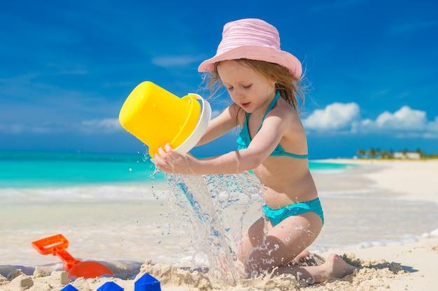 Маленькая милая девушка играет с игрушками пляж во время тропического отпуска
