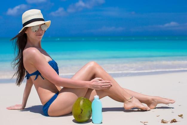 若い女性は彼女の滑らかな日焼けした足にクリームを適用します