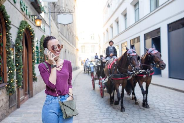 女性は街で彼女のスマートフォンで話します。