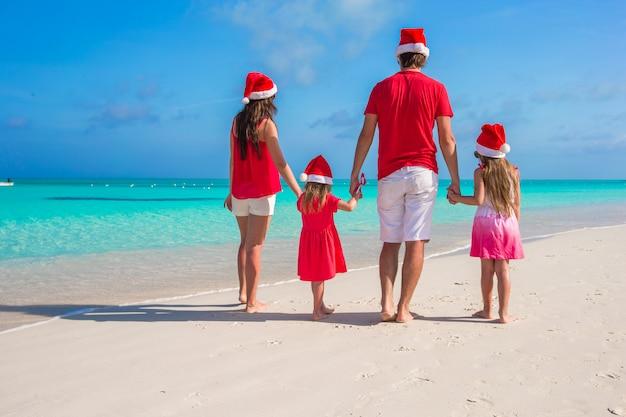 Счастливая семья из четырех человек в санта-хэт на летних каникулах