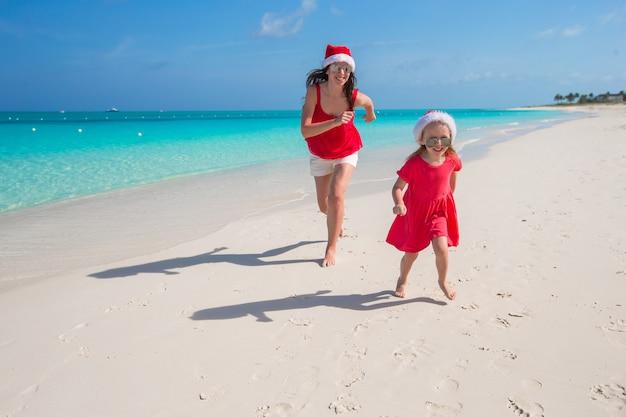 Молодая мать и маленькая девочка развлекаются на тропическом пляже