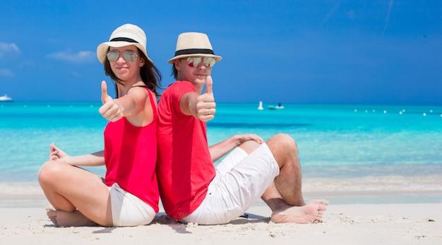 Счастливая молодая пара на тропическом белом пляже