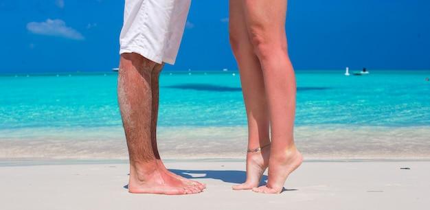 Закройте мужские и женские ноги на белом песке
