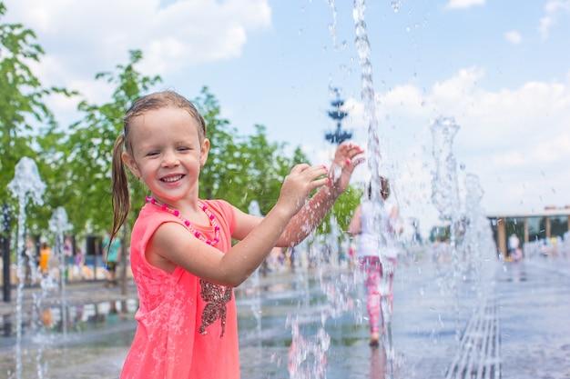 幸せな少女は、暑い晴れた日に通りの噴水で楽しい時を過す