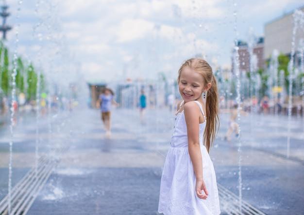 小さな女の子は暑い夏の日にオープンストリート噴水で楽しい時を過す