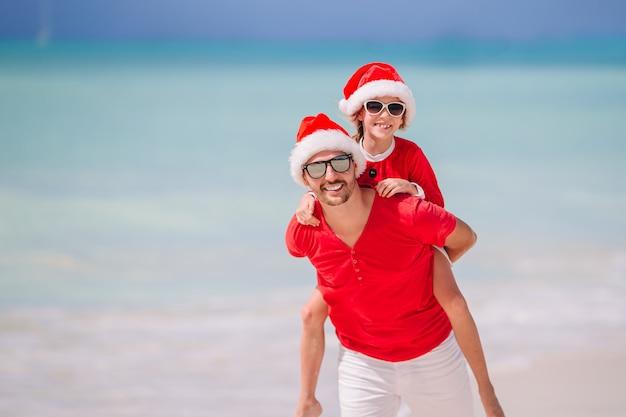 Отец и дочь в шляпе санта весело провести время на тропическом пляже