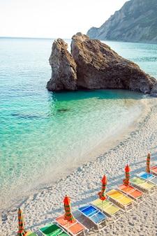 サンベッドとイタリア、チンクエテッレ、リグーリア州のモンテロッソの美しいヨーロッパの海岸で傘