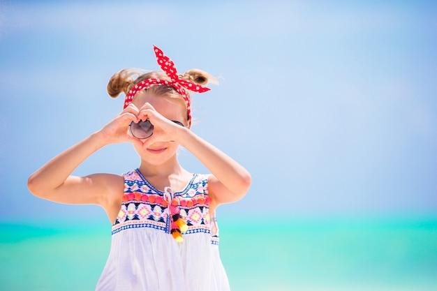 Маленькая девочка на пляже во время карибских каникул. портрет красивый малыш фон голубое небо