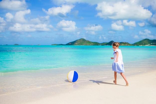 Прелестная маленькая девочка играя с шариком на пляже. детский летний спорт на открытом воздухе на карибском острове