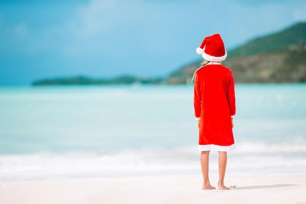 熱帯のビーチのサンタ帽子でのかわいい女の子