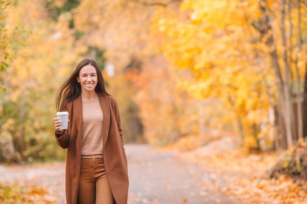 Осень концепция - красивая женщина пьет кофе в осеннем парке под осенней листвой