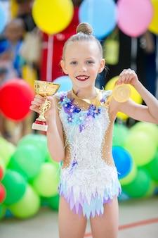 Красивая маленькая гимнастка тренируется на ковре и готова к соревнованиям