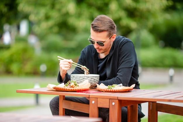 Молодой человек ест забрать лапшу на улице