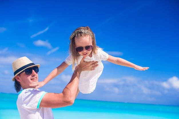 若いお父さんと愛らしい小さな娘は、熱帯のビーチでの休暇で楽しい時を過す