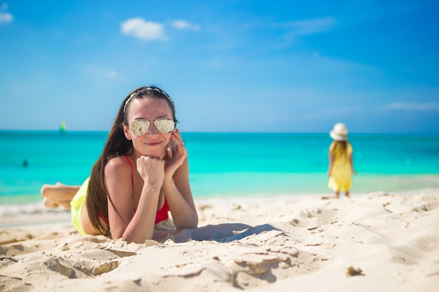 白い砂の上に横たわると彼女の電話で話している若い女性