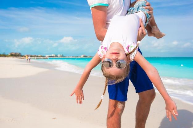 幸せなパパは、ビーチでの休暇中に彼の小さなかわいい女の子と楽しい時を過す