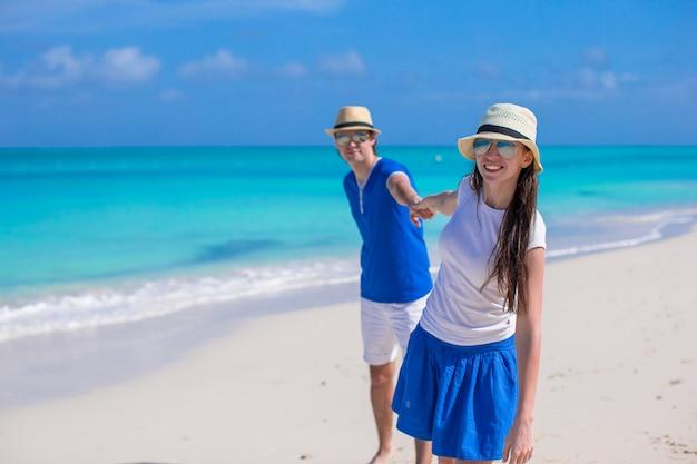 幸せな家族がカリブ海のビーチでの休暇を楽しんでください。