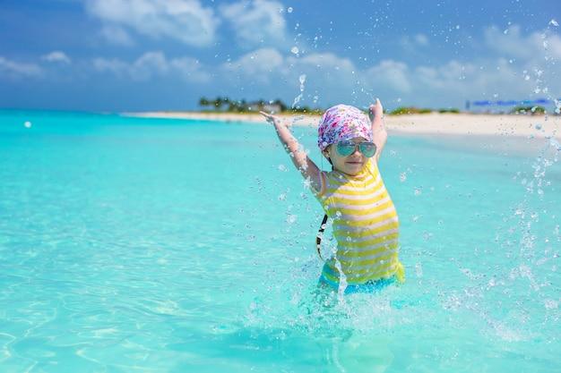幸せな少女は、夏休みの間にビーチで楽しい時を過す