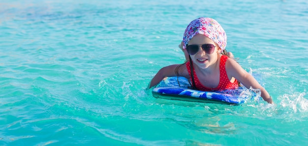 ターコイズブルーの海でサーフボードに愛らしい少女