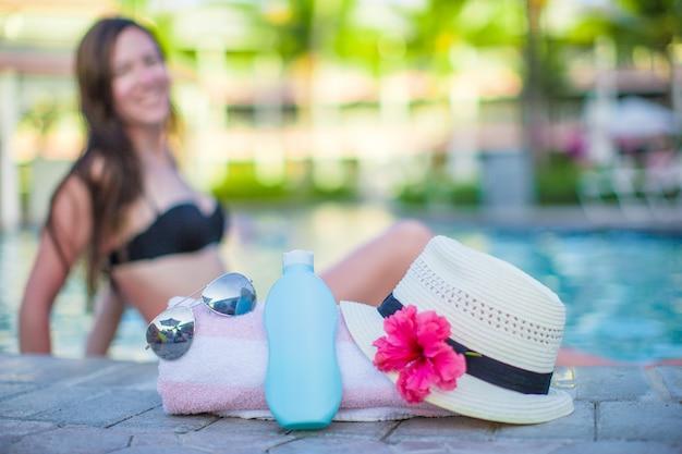 女性、サンクリーム、帽子、サングラス、花、スイミングプールのそばの塔