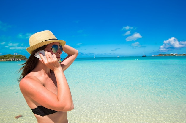 熱帯のビーチで彼女の電話で若い女性の話