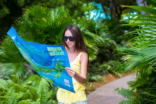 Молодая привлекательная женщина с большой картой острова в джунглях