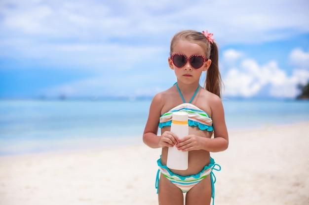 水着の愛らしい少女は日焼け止めローションボトルを保持します
